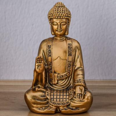 Cette statue représente un Bouddha de couleur or en position de méditation.